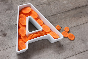 Vitamin A in food concept. Plate in the shape of the letter A with sliced fresh carrots.