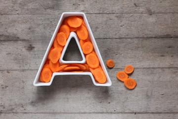 Vitamin A in food concept. Plate in the shape of the letter A with sliced fresh carrots on wooden background. Flat lay.
