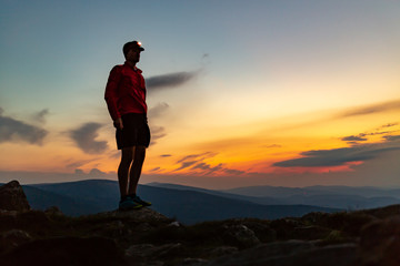 Trail runner with head lamp on top of mountain peak at night.