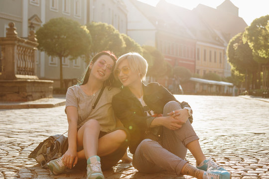 beautiful young women sitting on cobbled street together on sunset