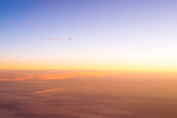the plane flies in the clouds during sunset