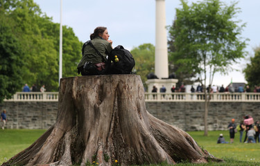 Woman sits on tree stump before demonstrations during the G7 Summit in Quebec City