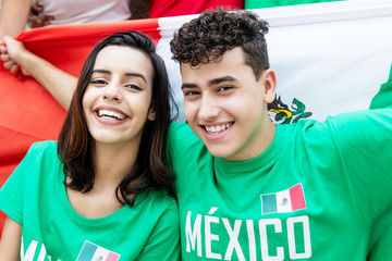 Soccer fans from Mexico with mexican flag looking at camera