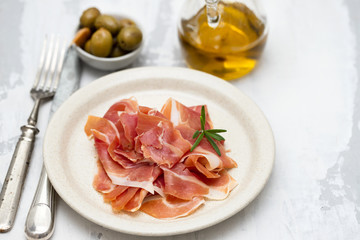 prosciutto on dish with olive oil and olives
