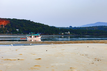 Tropical beach with fishing boats, Mobor Beach, South Goa, India
