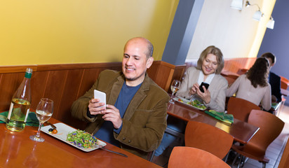 Mature man with mobile at the table in cafe.