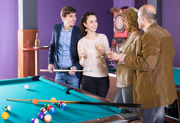 Mature and young couples hanging out in billiard club together