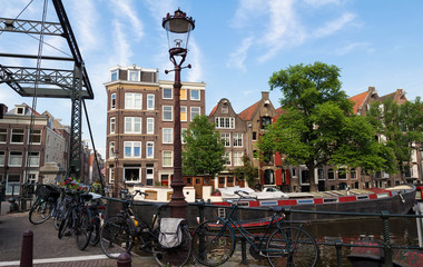 Beautiful view of Amsterdam canal with bridge and typical dutch houses. Holland