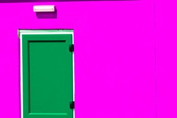 Vibrant colorful paint. Green painted door on neon pink building.