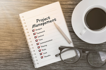 Project management and check list marks in notebook with glasses, pencil and coffee cup on wooden table. Project management concept.