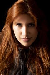 Redhead latin girl with black jacket on black background