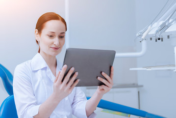 Online call. Attentive female holding tablet in both hands and smiling while looking downwards