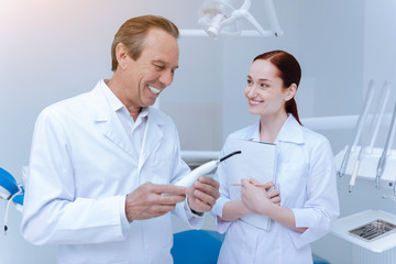 Healthcare. Handsome professional dentist holding dental tool in both hands keeping smile on her face while looking at it
