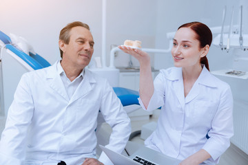 Artificial jaw. Attentive dentist keeping smile on his face and looking upwards while listening to his intern