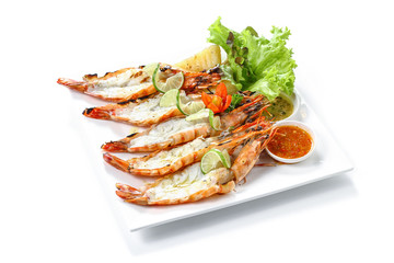 Roasted cleaved black tiger prawns with boiled potatoes, slice of limes, fresh vegetables and chilli sauce on white square plate, isolated on white background with shadow, high angle front side view.