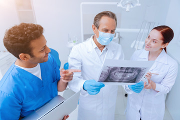 X-ray picture. Serious dentist wearing mask on face and looking straight at picture while explaining the meaning to his interns