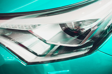 Close up shot headlight in luxury beige car background. Modern and expensive sport car concept