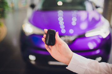 Female holding car keys with car on background purple color