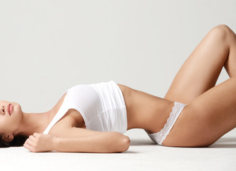 Beautiful woman lying on floor with legs up  isolated on white