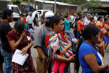 Residents wait in line to receive aid at an area affected by the eruption of Fuego volcano at the village of Sangre de Cristo in Chimaltenango
