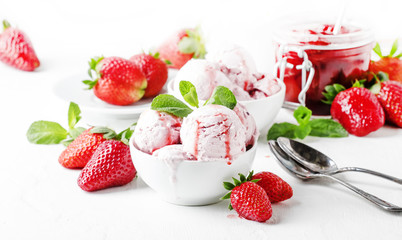 Strawberry ice cream with jam topping, decorated with green mint leaves, gray background, selective focus
