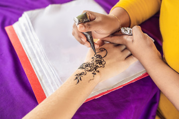 Woman is drawing on hand. Draw on the hand Indian mehendi picture