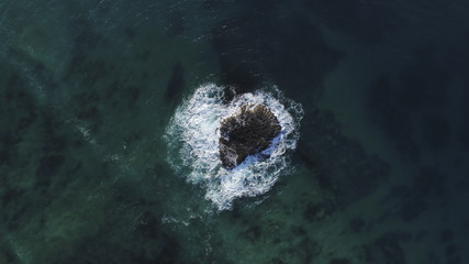 Aerial View of Waves Washing over Rock in Middle of Ocean