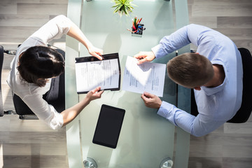 Elevated View Of Two Businesspeople Holding Resume