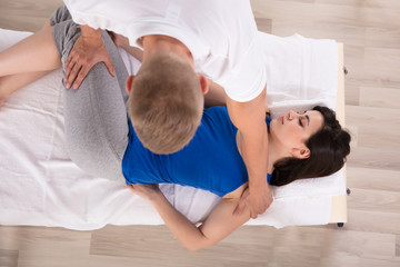 High Angle View Of A Woman Receiving Massage By Therapist