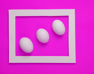 Three  chicken eggs in a white frame. Minimalist trend..