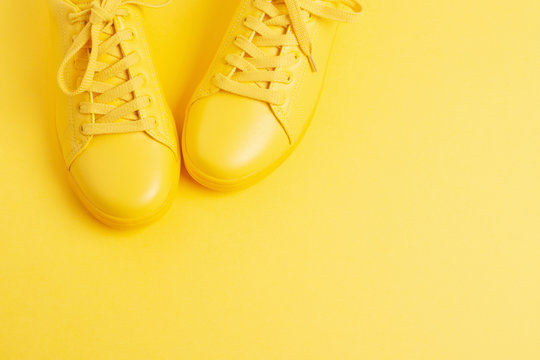 Pair of yellow shoes on yellow background. Trendy summer color, monochrome image. Hipster concept. Shot at angle.