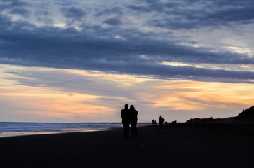 Couple walking in the beach at sunset