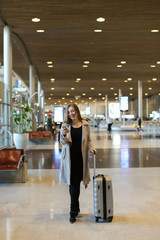 Caucasian young female person going in airport waiting room with valise and chatting by smartphone. Concept of traveling abroad and communication by mobile phone, free hotspot.