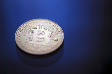 Bitcoin coin on blue light background