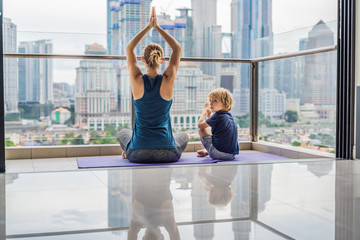 Mom and son are practicing yoga on the balcony in the background of a big city. Sports mom with kid doing morning work-out at home.