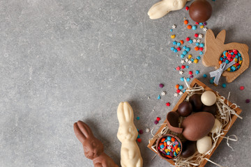 Beautiful Easter composition with chocolate bunnies, eggs and sprinkles on gray background