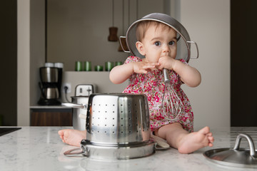Cute baby sitting on kitchen counter with colander on head playing with kitchenware