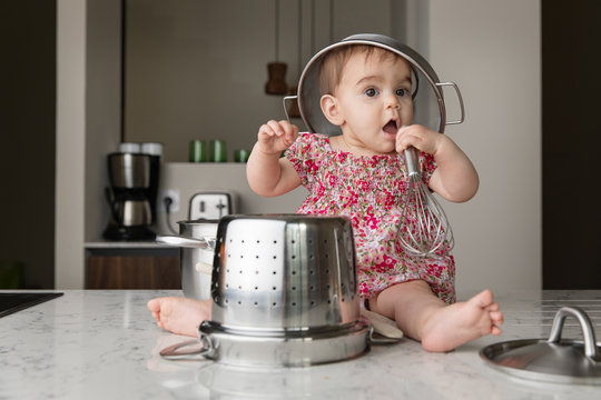 Baby sitting on kitchen counter with colander on head