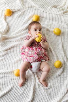 Baby lying on blanket holding a lemon