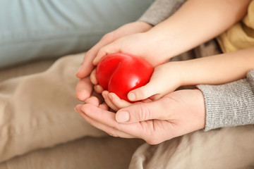 Hands of mother and her little daughter holding red heart, closeup