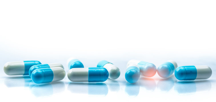 Blue and white capsules pill spread on white background with shadow and copy space. Global healthcare concept. Antibiotics drug resistance. Antimicrobial capsule pills. Pharmaceutical industry.