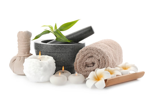 Spa composition with mortar, candles and clean towel on white background