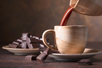 Cup of hot chocolate and bitter chocolate pieces.