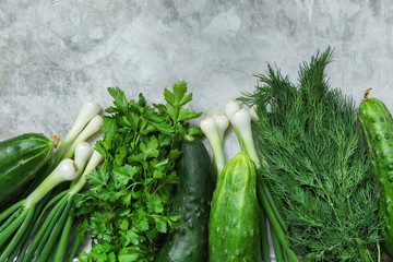 Bunch of Fresh Garden Herbs Greenery Parsley Dill Scallions Cucumbers on Grey Cement Concrete Metal Stone Background. Superfoods Healthy Diet Vitamins Vegan Concept. Vivid Colors. Copy Space