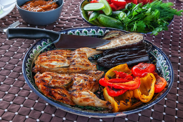 Grilled tobacco chicken with sauce on a stone plate with Bulgarian fried red pepper eggplant zucchini and garlic. Delicious dinner.