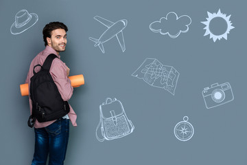 Travelling abroad. Cheerful young tourist feeling confident and turning with a smile while travelling abroad with a backpack and a yoga mat