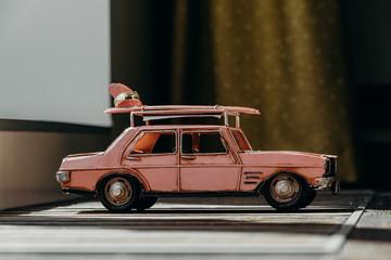 Toy retro car, wedding rings lying on roof car.