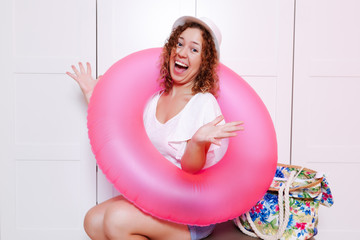 Woman sitting on luggage with inflatable round and ready for vacation trip. Preparing for the vacation concept
