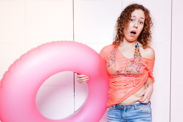 Woman point to her belly and hold an inflatable round. Preparing for the vacation, diet concept, unready for vacation
