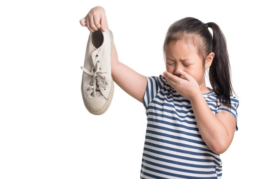 Asian kid girl age 7 year hold stinky shoe on white background